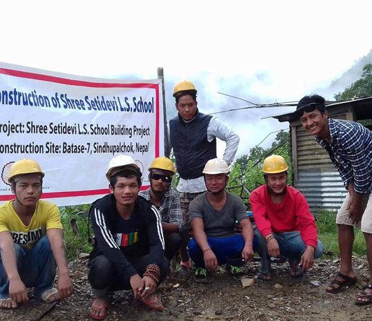Equipe des ouvriers népalais devant la banderole de la reconstruction